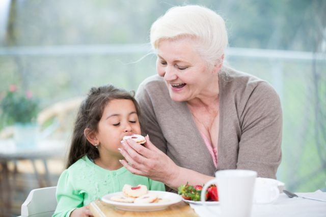 Бабушка кормит внучку